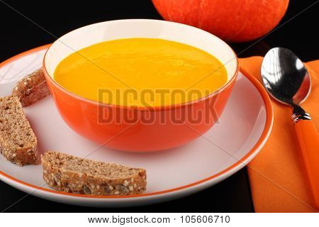 Bowl Of Pumpkin Hokkaido Soup With Bread  On White Plate On Black Sheet