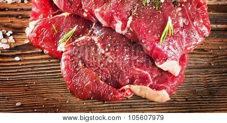 Beef Steak With Seasoning And Fresh Herbs On  Wooden Board.