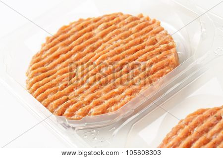 detail of package of raw burger patties on white background