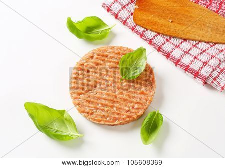 raw burger patty with basil on white background