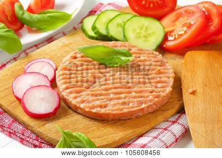 close up of raw burger patty and vegetables on wooden cutting board