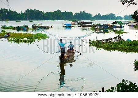 Unidentified fisher throw fish net in a lake on October 12, 2014 in Angiang, Vietnam