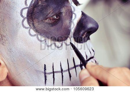 closeup of a young man making up himself as a mexican sugar skull