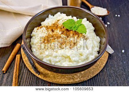Rice Porridge With Cinnamon In Bowl On Dark Board