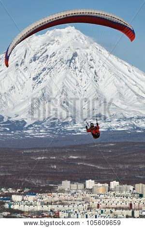 Paraglider Flying Over City On Background Of Active Volcano