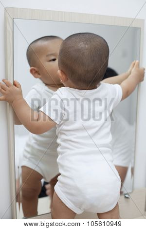 Chinese baby boy playing in front of a mirror