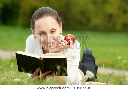 young woman smilling and reading book