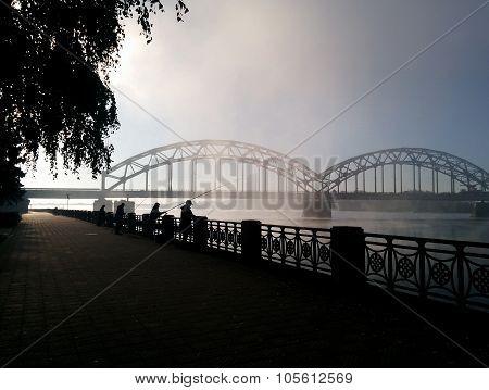 Fisherman's On The Daugava Embankment And Railway Bridge. Foggy Morning View
