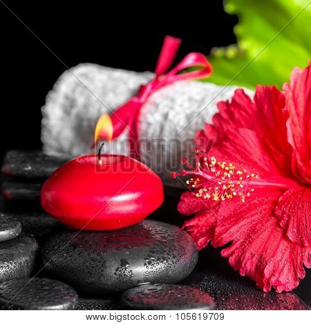 Beautiful Spa Composition Of Red Hibiscus Flower With Dew, Candles, Green Leaf And Rolled Towel Tied