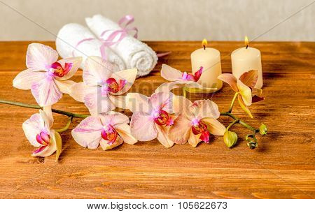 Beautiful Spa Concept Of Blooming Twig Orchid Flower, Phalaenopsis, White Towels And Candles On Wood