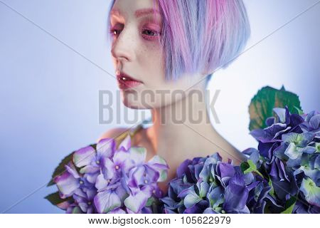 unusual girl with blue flowers, focus on flower