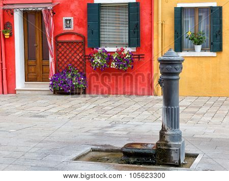 Venice, Burano: The Small Yard With Bright Walls Of Houses And A Stand-pipe