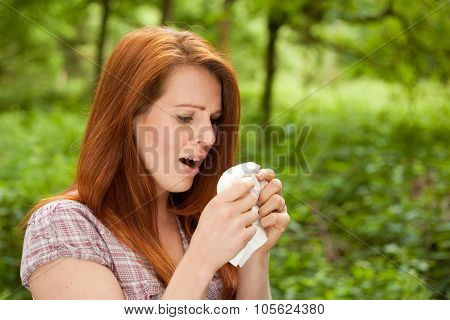 Young woman is sneezing in her tissue