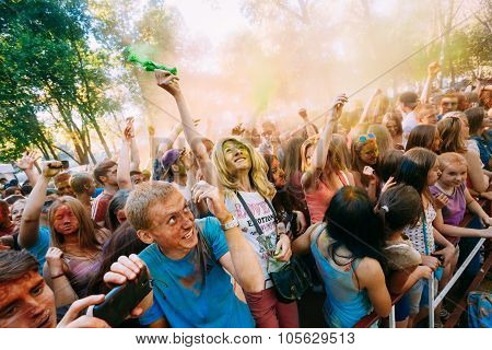 Young people having fun and dancing together at Holi color festival