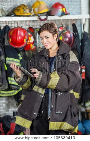 Portrait of happy firewoman in uniform using digital tablet at fire station