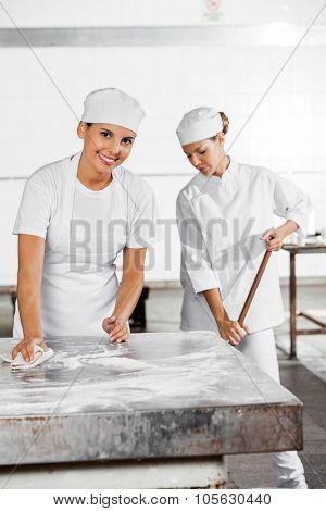 Portrait of confident female baker cleaning table while coworker using mop in bakery