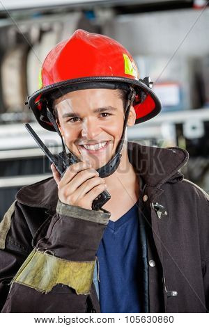 Portrait of smiling young fireman using walkie talkie at fire station