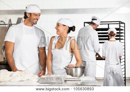 Happy male and female Baker's looking at each other while working in bakery