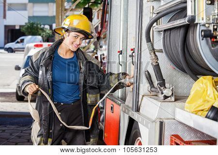 Portrait of smiling female firefighter adjusting water hose in truck at fire station