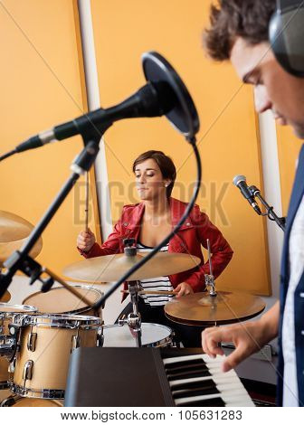 Young female drummer performing with male pianist in recording studio