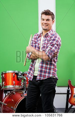 Portrait of confident male drummer standing arms crossed in recording studio