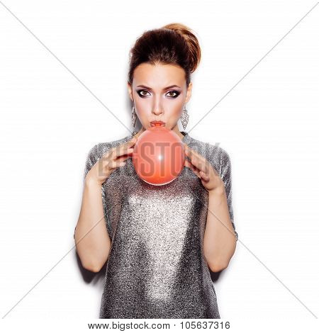 Fashion Beauty Girl Blowing A Red Balloon. Gorgeous Woman Portrait