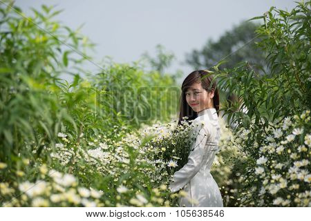 Vietnamese girl in traditional dress in white daisy flower garden