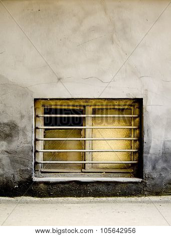 Dirty old window with bars on a grungy building
