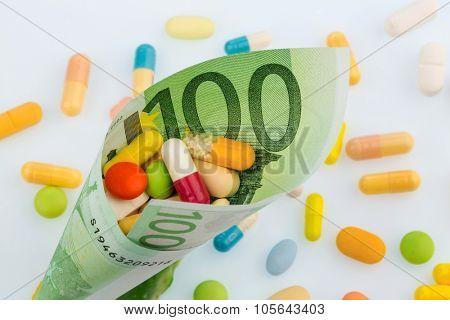 tablets and one hundred euro banknote symbol photo: cost of medicine and drugs in the pharmaceutical industry