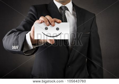 Businessman showing smile on business card