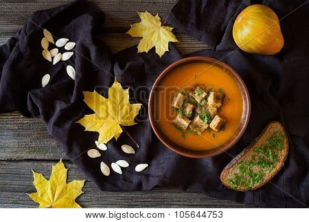 Healthy homemade traditional vegetarian pumpkin soup with croutons and fall leaves composition. Dark