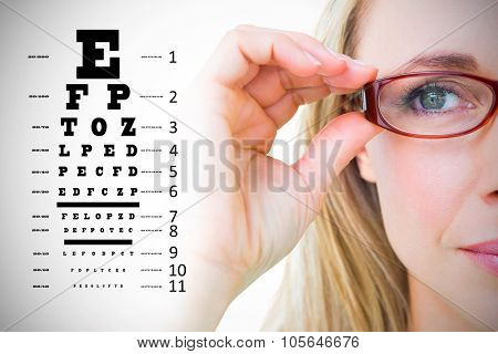 Close up of pretty blonde with red reading glasses against eye test