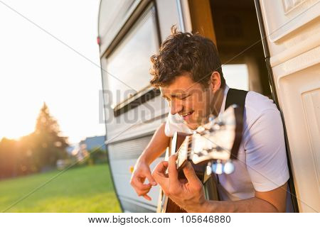 Young man sitting in a camper van