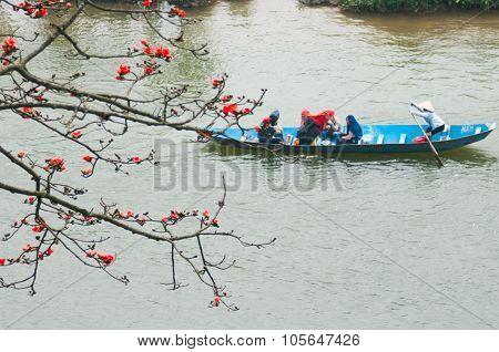 Tourist on boat visit Huong pagoda in bombax ceiba flower season.