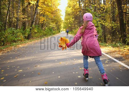 A girl in a pink jacket and helmet rolling on roller skates on the alley in autumn park, view from the back, motion blur