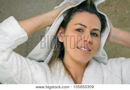 Young woman wiping wet hair with a towel