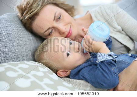 Mommy watching baby boy drinking from baby bottle