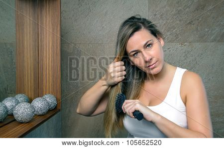 Beautiful young woman straightening hair with a straightener