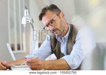 Trendy businessman with eyeglasses writing on agenda