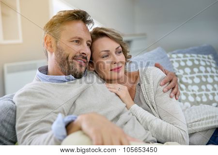 Mature couple relaxing in couch at home