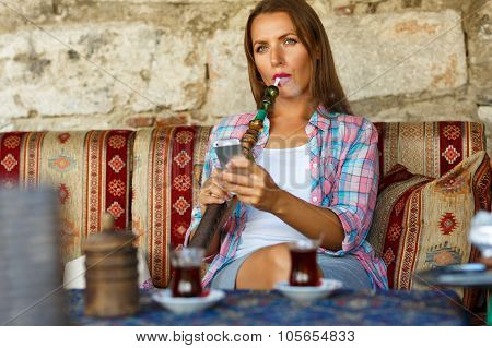 Woman Smoking A Hookah And Uses Smartphone In A Cafe In Istanbul, Turkey