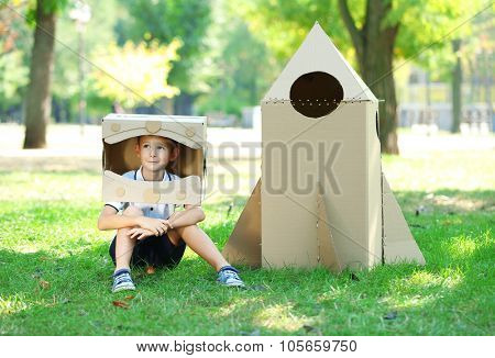 Funny boy in carton helmet sitting near carton rocket in  the park
