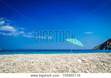 Beach Umbrella On Sunny Myrtos Beach, The Ionian Sea In Background.