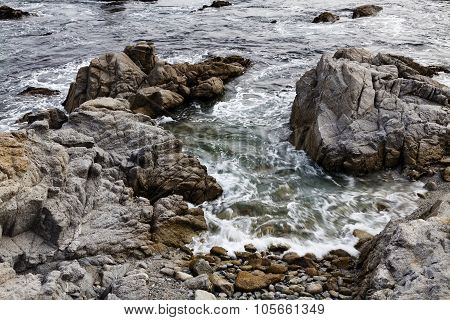 Ocean Water Surging On To Rocky Beach