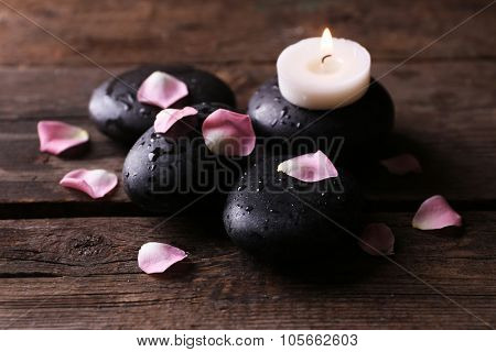 Alight candle and pebbles covered with rose petals on wooden background