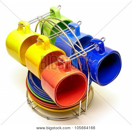 Multi-colored tea cups and saucers on metal support on a white background