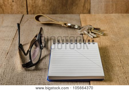 Blank Notepad, Key Chain And Eye Glasses On Wooden Table