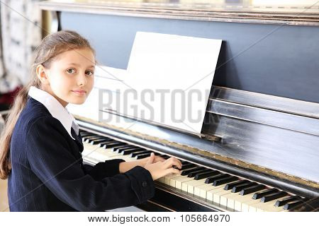 Attractive little girl plays piano