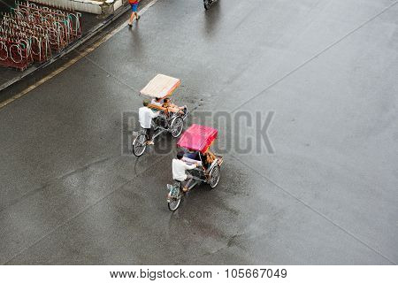 Cyclos drivers carry tourists in rainy day in Hanoi, Vietnam.