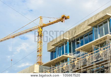 High-rise building under construction. The site with cranes against blue sky